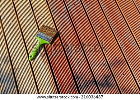 painting wooden patio deck with protective oil - stock photo
