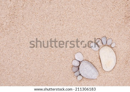 pair feet made of a stone on the sea sand  - stock photo