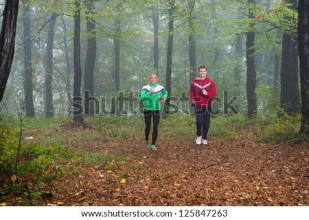 pair jogging in autumnal woodland with fog - stock photo