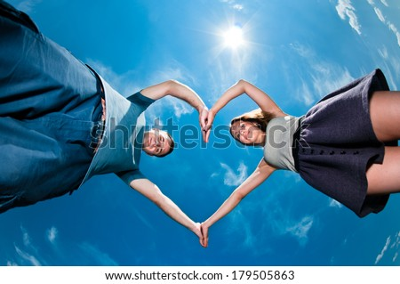 Pair making heart symbol with their hands at day time - stock photo