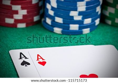Pair of aces on a poker table with poker chips next to them - stock photo