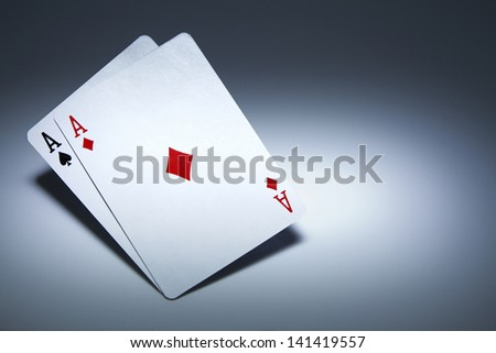 Pair of Aces playing cards balanced on white. Gambling concept - stock photo
