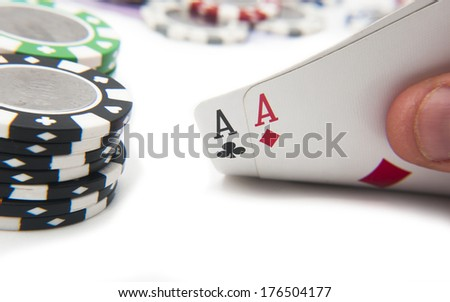 Pair of aces poker hand in front of poker chips stack - stock photo