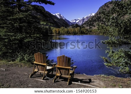 Pair of Adirondack Chairs sitting by lake - stock photo