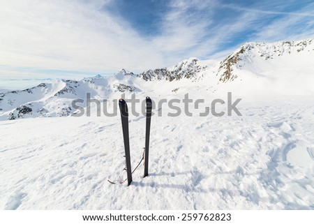 Pair of back country ski on the mountain summit. Shot in backlight, stunning panoramic view of the alpine arc with clouds covering the valleys below. Concept of success and conquering the top. - stock photo