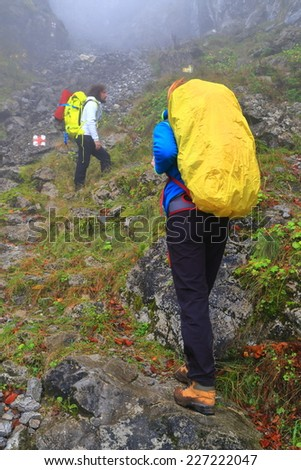 Pair of backpackers climb a rocky trail in the morning mist - stock photo