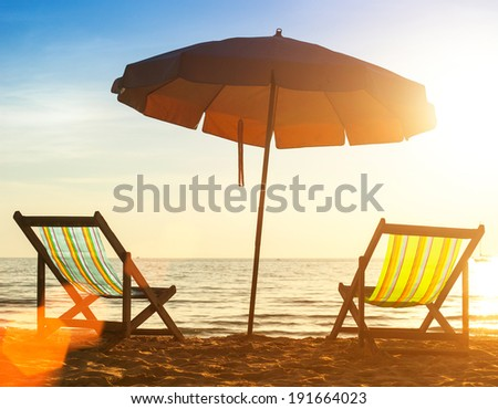 Pair of beach loungers on the deserted coast sea at sunrise. - stock photo