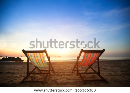 Pair of beach loungers on the deserted coast sea at sunrise, perfect vacation concept. - stock photo