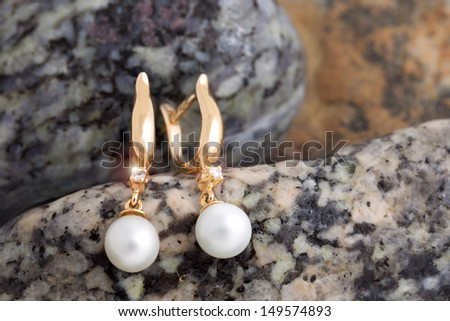 Pair of Beautiful  Gold Earrings with Diamonds and Pearls on the natural stones background - stock photo