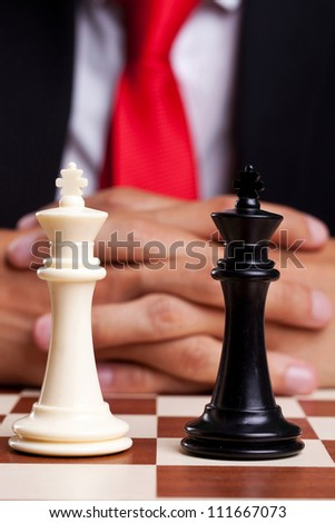 Pair of black and white chess kings in front of businessman - stock photo