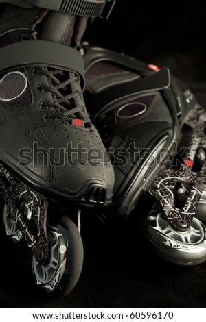 Pair of black rollerblades on black background - stock photo