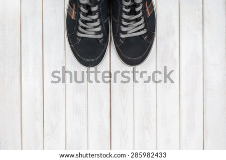 Pair of black sneakers on white wooden background. View from above - stock photo