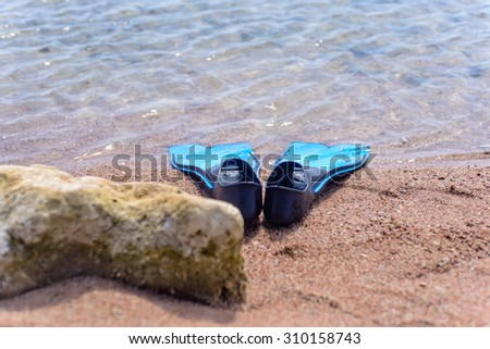 Pair of blue rubber fins or flippers on the seashore lying alongside a rock at the edge of the ocean ready to go swimming or skin diving - stock photo