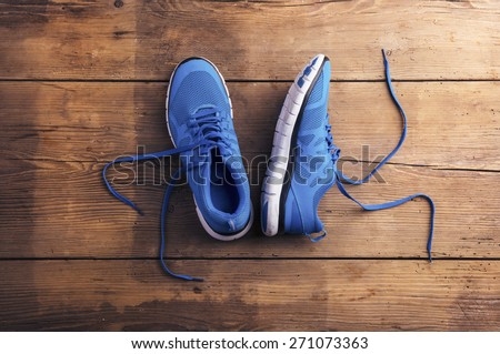 Pair of blue running shoes laid on a wooden floor background - stock photo