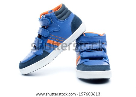Pair of blue sneakers in children size, isolated on white background. - stock photo