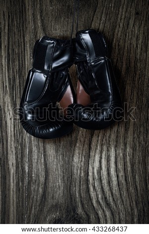 Pair of boxing gloves hanging on wooden wall. - stock photo