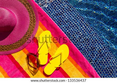 Pair of bright yellow flip flops by the pool on a bright orange, pink, red and yellow striped towel with sunglasses and big pink floppy hat - stock photo