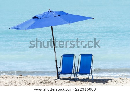 Pair of chairs and an umbrella on the beach of Ponta Verde, Maceio, Alagoas, northeast of Brazil - stock photo