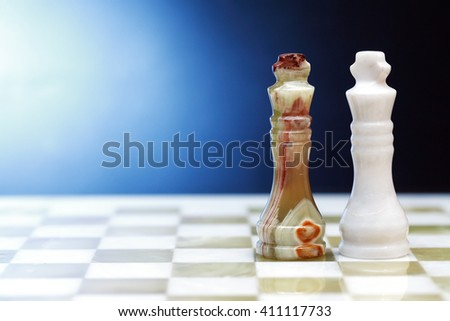 Pair of chess Kings made from Onyx on board against dark background - stock photo