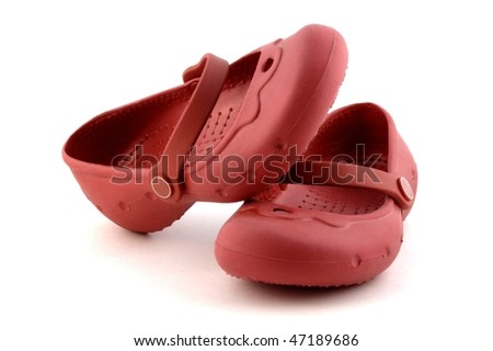Pair of child red rubber shoes on white background - stock photo