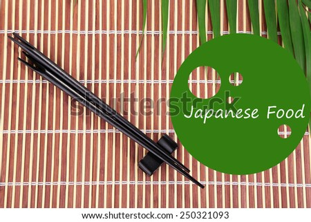 Pair of chopsticks and Japanese Food text on bamboo mat background - stock photo