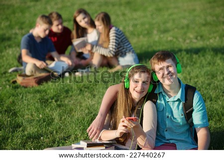 Pair of cute teens with cell phone and earphones - stock photo