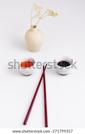 Pair of dark wood chopsticks set on white surface with clay jars of chili & soy sauce on either side & clay vase with baby's breath flowers in the background - stock photo