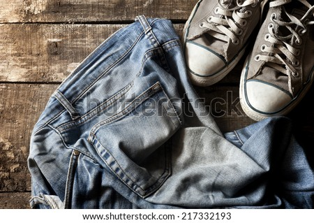 Pair of dirty jeans thrown on floor with a pair of sneakers - stock photo