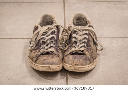 Pair of dirty shoes with mud on the floor - stock photo