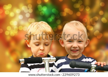 Pair of disappointed and happy blond boys in the striped shirts  on a scooters. Blurred Christmas background. - stock photo