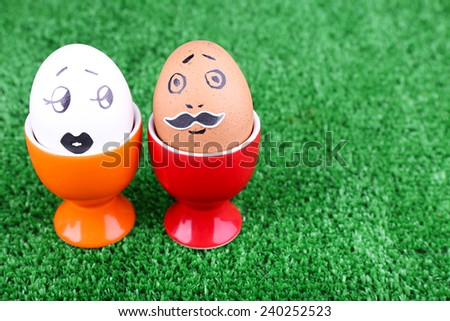 Pair of eggs in egg cups on green background - stock photo