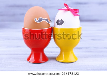 Pair of eggs in egg cups on grey wooden background - stock photo