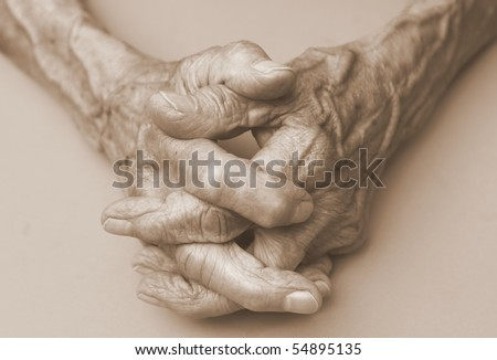 pair of elderly wrinkled hands in prayer - stock photo