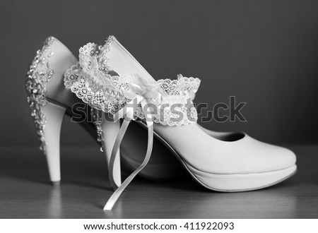pair of elegant wedding shoes with garter - stock photo