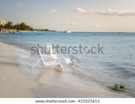 Pair of empty Plastic Chairs on the  Sandy Shore of a Crowded Tropical Beach - stock photo