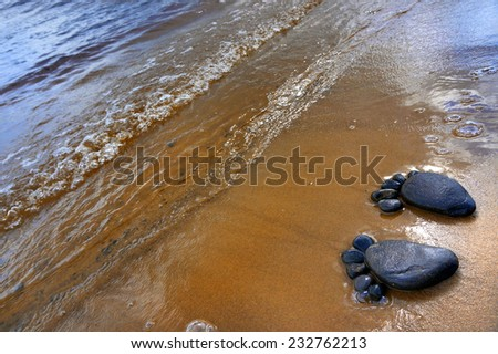 pair of feet made from pebbles on the sea sand  texture surface backdrop                        - stock photo