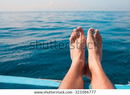 Pair of feet resting on boat. - stock photo