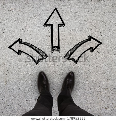 pair of feet standing on a tarmac road with color arrows - stock photo