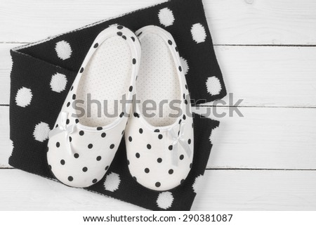 Pair of feminine slippers with white and black polka dot decor and woolen scarf on white wooden floor. - stock photo