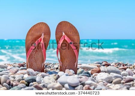 Pair of flip flops on pebble beach. Rhodes, Greece - stock photo
