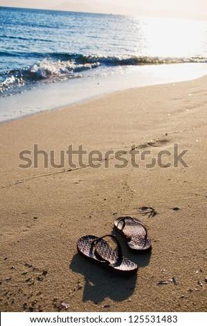 Pair of Flip Flops on sandy Beach - stock photo