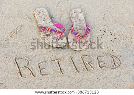pair of flip-flops on the beach with word retired printed in sand - stock photo