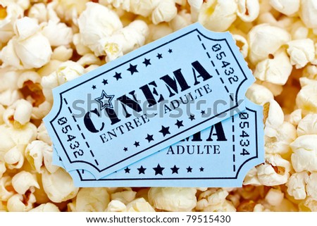 Pair of french cinema tickets on popcorn background - stock photo