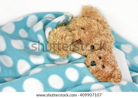 pair of fuzzy brown teddy bears snuggling under a polka dot blanket - stock photo