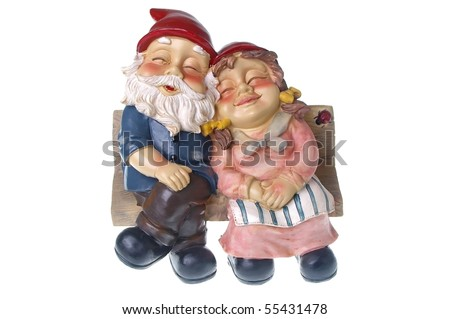 pair of garden gnomes in love together on chair - stock photo
