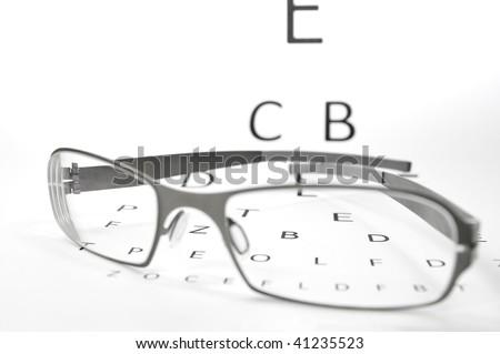 pair of glasses lying on an eyesight test - stock photo