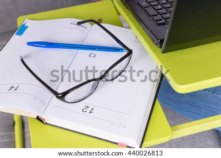 Pair of glasses lying on the laptop table near open blank page of a business journal or diary with a pen for making appointments, organising a schedule or agenda - stock photo