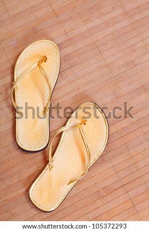 Pair of golden flip flops on the bamboo mat. - stock photo