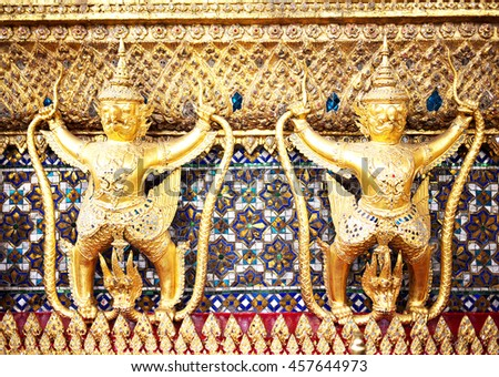 Pair of golden Garuda statues at the temple wall in the Grand Palace, Bangkok, Thailand. - stock photo