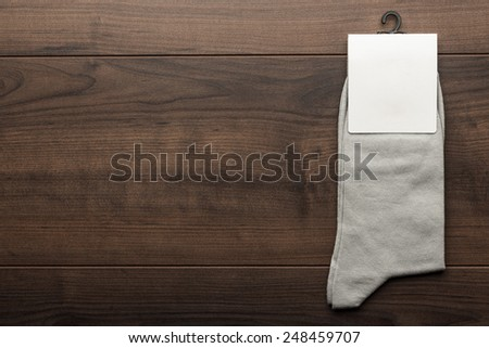pair of gray socks with blank packing on the wooden table - stock photo